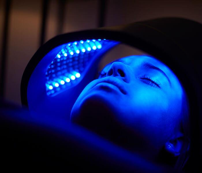 Closeup of a woman's head inside the LED Light Therapy machine, under a blue light